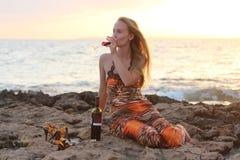 Una mujer hermosa que se sienta en la playa y el vino de consumición Foto de archivo libre de regalías