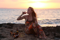 Una mujer hermosa que se sienta en la playa y el vino de consumición Imágenes de archivo libres de regalías