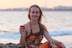 Una mujer hermosa que se sienta en la playa y el vino de consumición Imagen de archivo