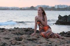 Una mujer hermosa que se sienta en la playa y el vino de consumición Imagen de archivo libre de regalías
