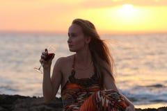 Una mujer hermosa que se sienta en la playa y el vino de consumición Fotografía de archivo
