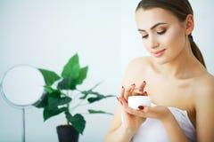 Una mujer hermosa que usa un producto para el cuidado de la piel, una crema hidratante o un loti fotos de archivo