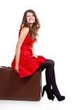 Una mujer hermosa se está sentando en un equipaje Imagen de archivo