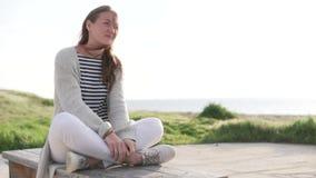 Una mujer hermosa se está sentando en un puente cerca del mar almacen de video
