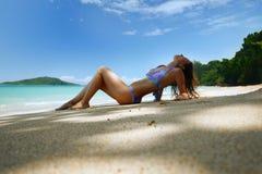 Una mujer hermosa toma el sol en una playa contra el contexto de t Fotografía de archivo