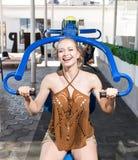 Una mujer hermosa y sana en un aparato del entrenamiento Una muchacha de risa en un fondo soleado de la reconstrucción Una señora Foto de archivo