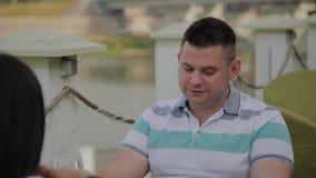 Una mujer hermosa y un hombre se están sentando en una tabla en un restaurante en una terraza abierta almacen de video