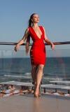 Una mujer imponente en un vestido rojo en un fondo natural Una muchacha que se relaja en una terraza del hotel Una muchacha perfe Imagenes de archivo