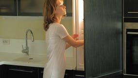 Una mujer joven abre el refrigerador, elige productos Ma?ana almacen de video