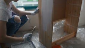 Una mujer joven adorna los muebles almacen de metraje de vídeo