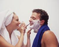 Una mujer joven afeita a su marido Foto de archivo libre de regalías