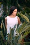 Una mujer joven apuesta está presentando en el fondo natural de las hojas La muchacha hermosa con el pelo largo del marrón oscuro Foto de archivo