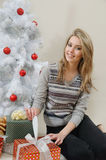 Una mujer joven atractiva abre un regalo el mañana de la Navidad Foto de archivo