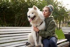 Una mujer joven atractiva con los dreadlocks se sienta en un banco de parque con su perro blanco como la nieve del samoyedo foto de archivo