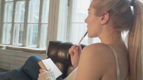 Una mujer joven atractiva escribe un nudo que miente en una silla Un blonde hermoso hace notas en una libreta con una pluma Una m metrajes