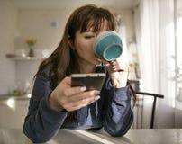 Una mujer joven bebe de una taza en el fondo de la cocina, utiliza su teléfono imágenes de archivo libres de regalías