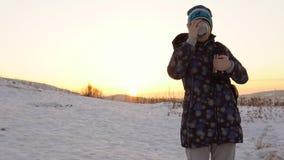 Una mujer joven bebe té caliente o un café del termo en las montañas en la puesta del sol almacen de video