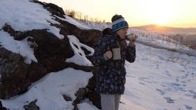 Una mujer joven bebe té o el café de un termo en una colina cerca de la ciudad almacen de metraje de vídeo