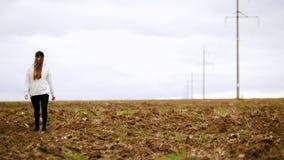 Una mujer joven bonita que camina en un campo del otoño almacen de video