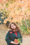 Una mujer joven camina en el parque del otoño Mujer morena que lleva una capa verde Ella está sosteniendo un ramo de hojas amaril foto de archivo