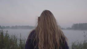Una mujer joven camina hacia el lago y sus oscilaciones largas del pelo en el viento almacen de video
