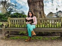 Una mujer joven casual que se sienta en un banco en un parque y una lectura Fotografía de archivo libre de regalías