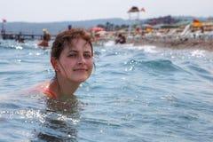 Una mujer joven caucásica que se baña en el mar cerca de la playa del centro turístico Fotos de archivo libres de regalías