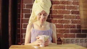 Una mujer joven come el yogur de un tarro blanco grande cerca de una pared de ladrillo almacen de video