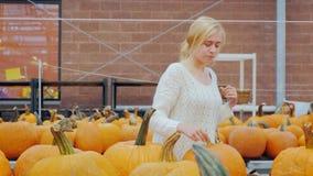 Una mujer joven compra una calabaza en una tienda grande Es rodeado por los contadores con una selección enorme de calabazas para almacen de metraje de vídeo