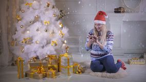 Una mujer joven comprueba su smartphone debajo de un árbol de navidad metrajes