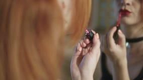 Una mujer joven con el pelo rojo delante de un espejo grande pinta sus labios en un color rojo brillante almacen de metraje de vídeo