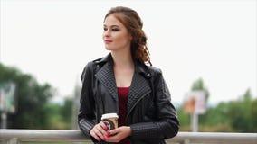 Una mujer joven con el pelo rojo y un café para llevar en sus manos mira fijamente lejos almacen de video