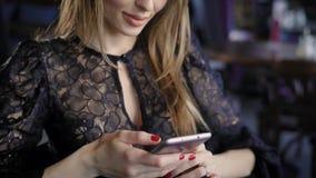Una mujer joven con el pelo rubio que lleva un suéter negro comunica con los amigos en redes sociales en su teléfono móvil almacen de video