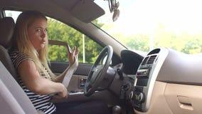 Una mujer joven con el pelo rubio sujeta su cinturón de seguridad en el coche almacen de video