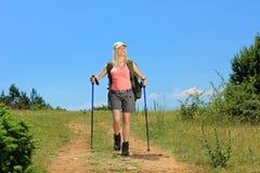 Una mujer joven con la mochila y caminar caminar de los polos Fotografía de archivo libre de regalías