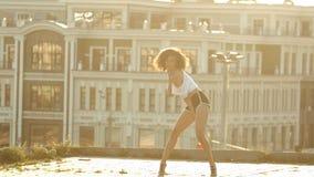 Una mujer joven con las piernas largas en los pequeños pantalones cortos que realizan el baile atractivo en el tejado - puesta de almacen de metraje de vídeo