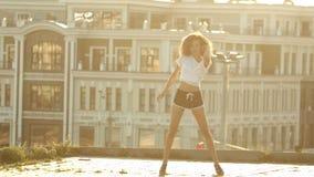 Una mujer joven con las piernas largas en los pequeños pantalones cortos que realizan el baile atractivo atractivo en el tejado - metrajes