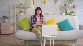 Una mujer joven con los vidrios utiliza la lengua del sordo para comunicar en Internet metrajes