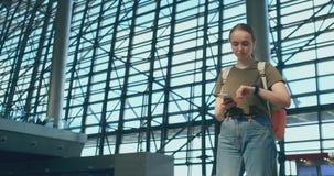 Una mujer joven con una mochila en el aeropuerto que mira alrededor almacen de metraje de vídeo