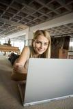 Una mujer joven con su computadora portátil Foto de archivo libre de regalías