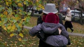 Una mujer joven con su hija está caminando en el parque, mamá es un niño almacen de metraje de vídeo