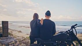 Una mujer joven con su novio, el jinete y su motocicleta admiran juntos la visión maravillosa alrededor, la montaña y almacen de video