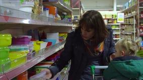 Una mujer joven con un niño en un supermercado elige mercancías La mamá está conduciendo a una niña en una carretilla Considere l almacen de video