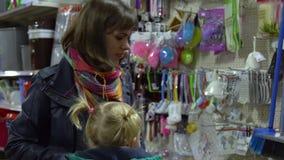 Una mujer joven con un niño en un supermercado elige mercancías La mamá está conduciendo a una niña en una carretilla Considere l metrajes