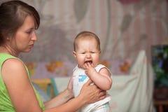 Una mujer joven con un niño está echando los dientes imagen de archivo