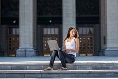 Una mujer joven con un ordenador portátil que se sienta en las escaleras, cerca del univ Foto de archivo libre de regalías