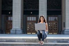 Una mujer joven con un ordenador portátil que se sienta en las escaleras, cerca del univ Foto de archivo