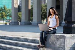 Una mujer joven con un ordenador portátil que se sienta en las escaleras, cerca del univ Fotografía de archivo libre de regalías