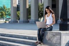 Una mujer joven con un ordenador portátil que se sienta en las escaleras, cerca del univ Imagenes de archivo