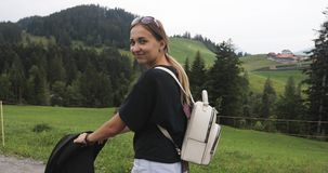 Una mujer joven con un pequeño niño en un carro de bebé camina en las montañas en verano metrajes